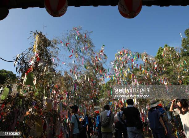 People walk under colorful paper strip decorations hung from bamboo branches during the Tanabata festival at the Hatamono shrine on July 7 2013 in...