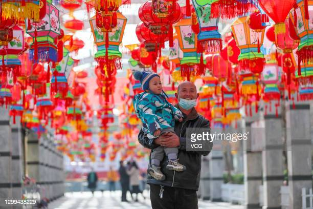 People walk under colourful lanterns set up at a park to mark the upcoming Chinese New Year, the Year of the Ox, on January 30, 2021 in Yuncheng,...