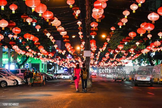TOPSHOT People walk under decorative lanterns ahead of the Chinese New Year in Yangon's Chinatown district on January 31 2019