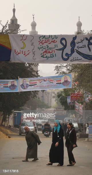 People walk under election banners near the Citadel on November 26 2011 in Cairo Egypt Thousands of Egyptians are continuing to occupy Tahrir Square...