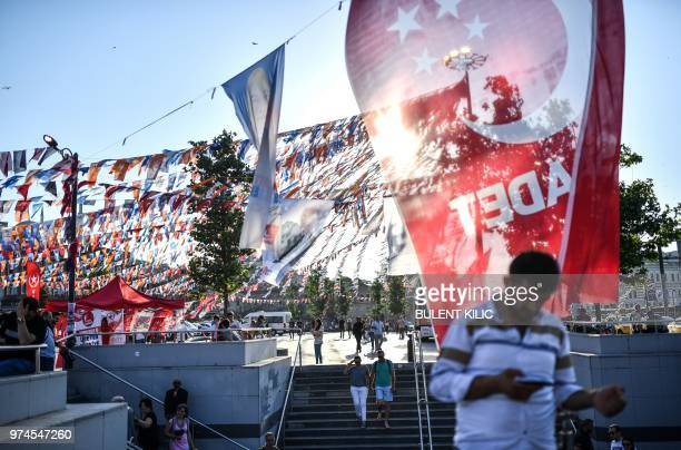 People walk under election flags for current Turkey's president and candidate of the ruling Justice and Development Party and for the opposition...