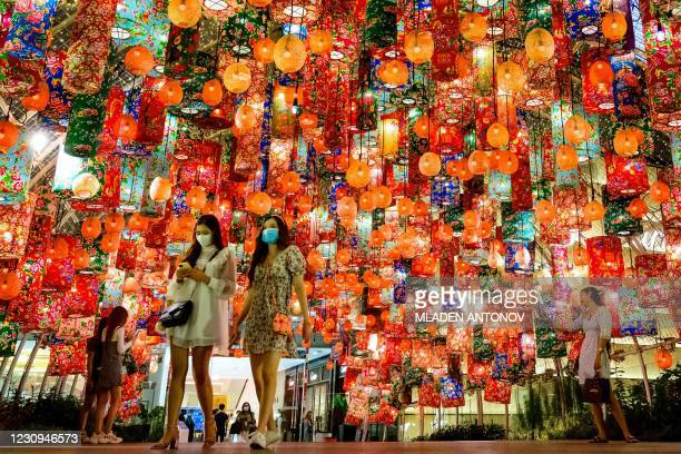 People walk under festive decorations for the upcoming Lunar New Year outside a shopping mall in Bangkok on February 3, 2021.