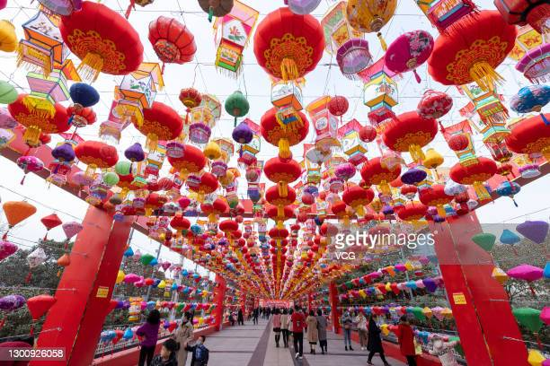 People walk under festive lanterns at a tourist attraction ahead of the Chinese New Year, the Year of the Ox, on February 7, 2021 in Yuncheng, Shanxi...