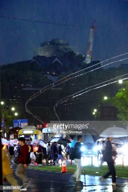 People walk under illuminated Kumamoto castle on the second anniversary of the Kumamoto Earthquakes on April 14 2018 in Kumamoto Japan The first of...