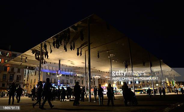 People walk under mirror panels designed by British architect Norman Foster on November 5 2013 on the Vieux Port in the southern French city of...