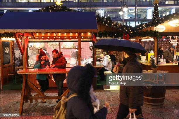 People walk under rain among stalls selling mulled wine sausages gingerbread candy and other delights at the annual Christmas market on its opening...