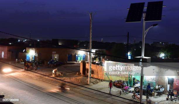 People walk under street lights using solar panels in a district of Agadez in northern Niger on April 5 2017 / AFP PHOTO / ISSOUF SANOGO