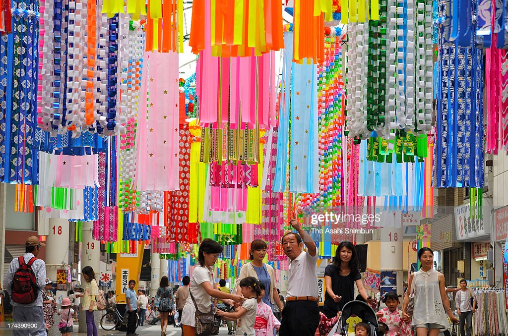 People walk under Tanabata ornaments during the Ichinomiya Tanabata Festival on July 25, 2013 in Ichinomiya, Aichi, Japan. Tanabata is a Japanese star festival, write their wishes on strips of paper to hang on bamboo trees.