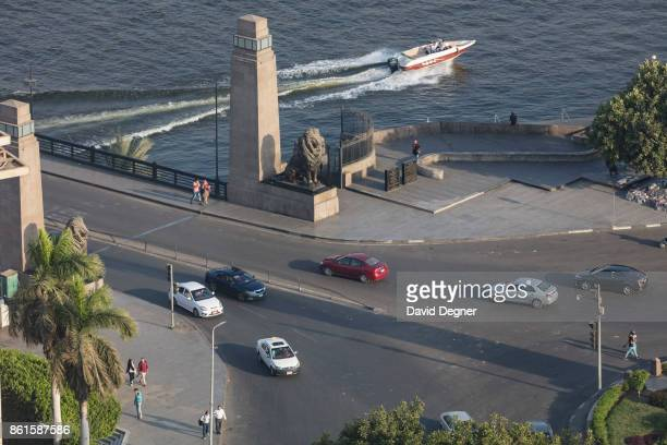 People walk under the lions of Qasr AlNile Bridge and boats pass under the bridge in front of the Cairo Opera House on September 24 2017 in Cairo...