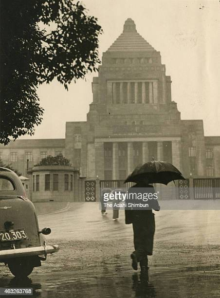 People walk under the rain in front of the diet building in February 1937 in Tokyo Japan