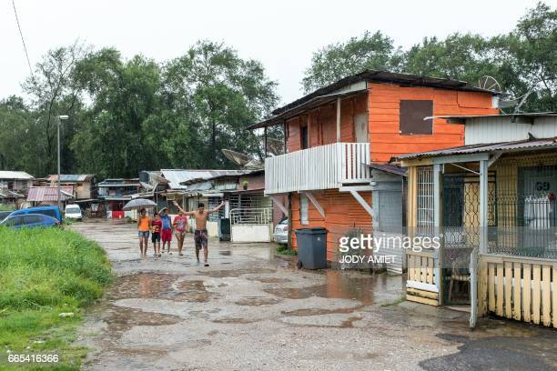 People walk under the rain on April 6 2017 in the district MatineLeblond of Cayenne French Guiana Air France canceled its scheduled direct flight of...