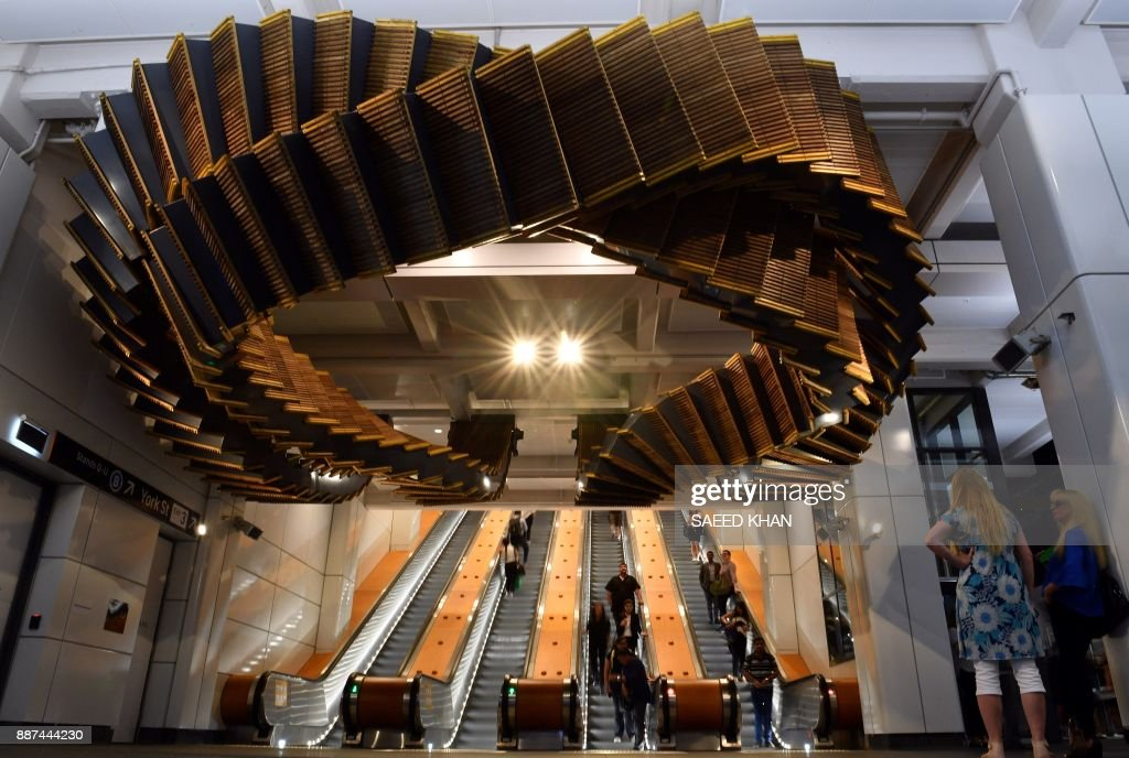 People walk under the sculpture 'Interloop', made from old wooden escalators in Wynyard railway station, by artist Chris Fox in Sydney on December 7, 2017. The decades-old wooden escalators in Wynyard station were replaced by modern escalators as part of the station's redevelopment. / AFP PHOTO / Saeed KHAN / RESTRICTED