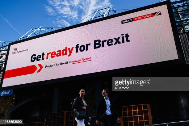 People walk underneath a 'Get ready for Brexit' billboard part of a huge government information campaign on Westminster Bridge Road in London England...