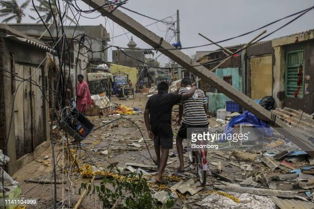 People walk underneath damaged electric cabling in Cyclone Fani passes in the Puri district of Odisha India on Saturday May 4 2019 A category 4 storm...
