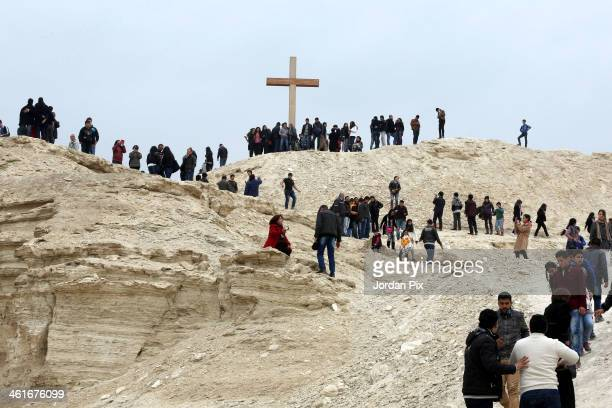 People walk up a hill to view a large cross next to the site of the Church of the Baptism of Jesus Christ following a service led by Latin Patriarch...