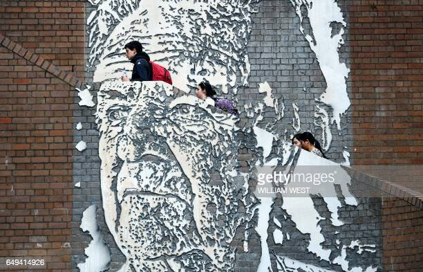 People walk up a staircase adorned with a mural by artist Alexandre Farto of Jack Mundey in the Rocks district of Sydney on March 2017. Mundey was a...