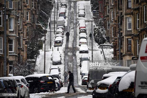 People walk up Gardner street in Glasgow on February 9, 2021 as snow blankets the city. - Cold weather swept across northern Europe bring snow and...