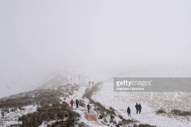 People walk up Pen y Fan mountain in the snow on January 03, 2021 in Brecon, Wales. The Met Office have issued a yellow weather warning for large...