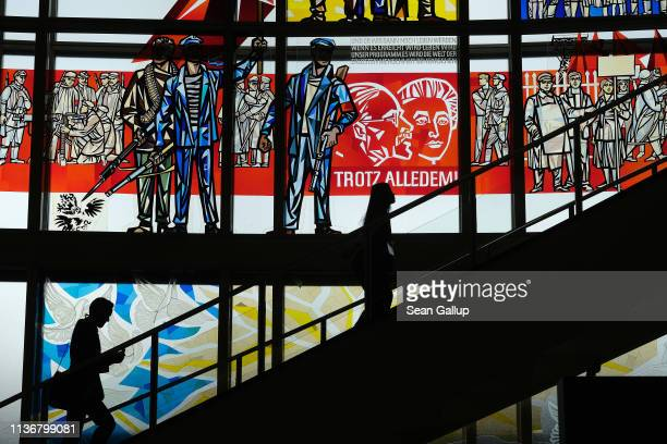 People walk up stairs next to a communistera stained glass Socialist Realist mural by artist Walter Womacka at the European School of Management and...