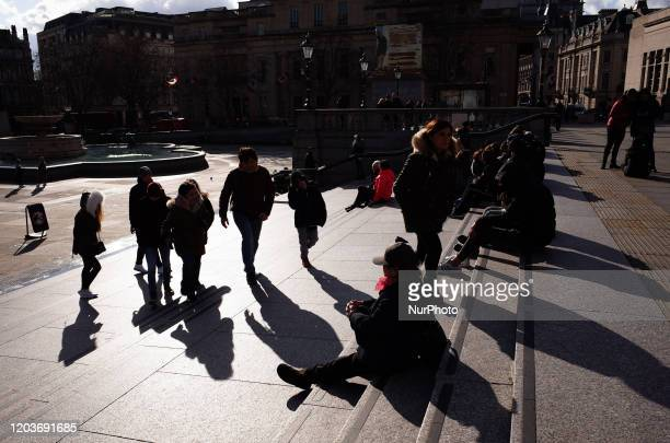 People walk up the steps to the North Terrace of Trafalgar Square in bright winter sunshine in London England on February 27 2020