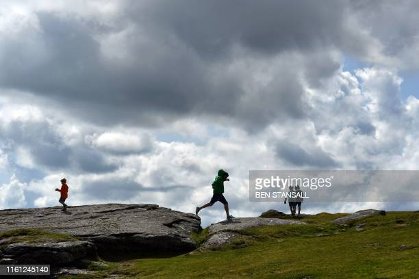 People walk up to Haytor Rocks in the Dartmoor National Park near Exeter southwest England on August 12 2019