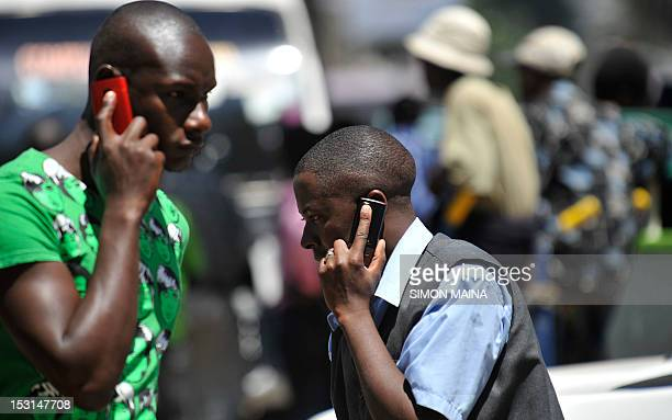 People walk while speaking on the phone on October 12012 in Nairobi as Kenya confirmed a switchoff of counterfeit mobiles will take place at the end...