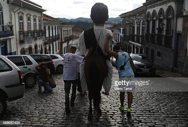 People walk with a costumed horse during traditional Semana Santa festivities on April 5 2015 in Ouro Preto Brazil Holy Week marks Easter...