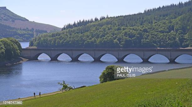People walk with a dog along the banks of Ladybower Reservoir near Bamford in the Peak District National Park in northern England on May 30, 2020 as...