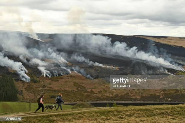 People walk with a dog as smoke is seen after a resurgence of the moor fire on Marsden Moor, near Huddersfield in northern England on April 27, 2021....