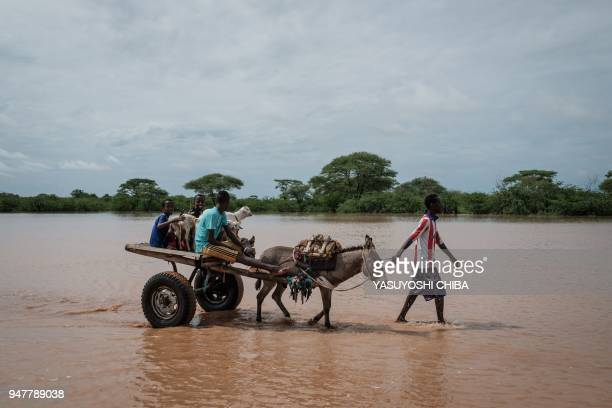 People walk with a donkey cart through floodwaters after a heavy rainy season downpour as they seek to fill sandbags at the Dadaab refugee complex,...