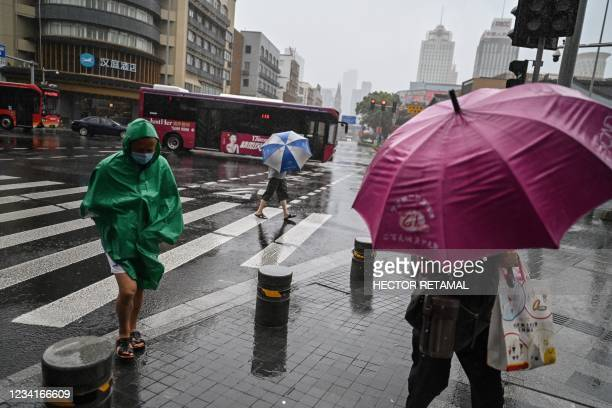 People walk with an umbrellas amid inclement weather in Ningbo, eastern China's Zhejiang province, on July 25 ahead of Typhoon In-Fa's expected...