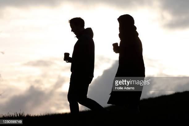 People walk with drinks as they do their daily exercise at Primrose Hill on January 15, 2021 in London, United Kingdom. With a surge of COVID-19...