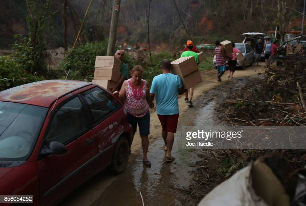 People walk with MRE's given to them by US Army 1st Special Forces Command soldiers who were delivering food and water to people after Hurricane...