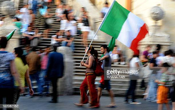 People walk with national flag as they wait in central Rome before the football game between Italy and Paraguay on June 14 2010 as part of the 2010...