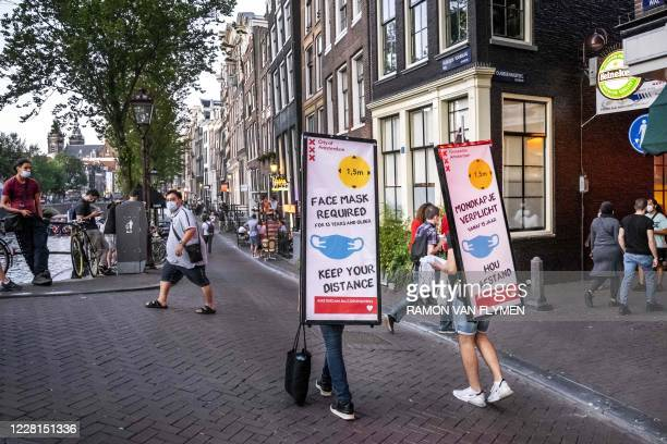 People walk with panels on their back reading 'face mask required, keep your distance', in the Red Light District in Amsterdam, The Netherlands, on...