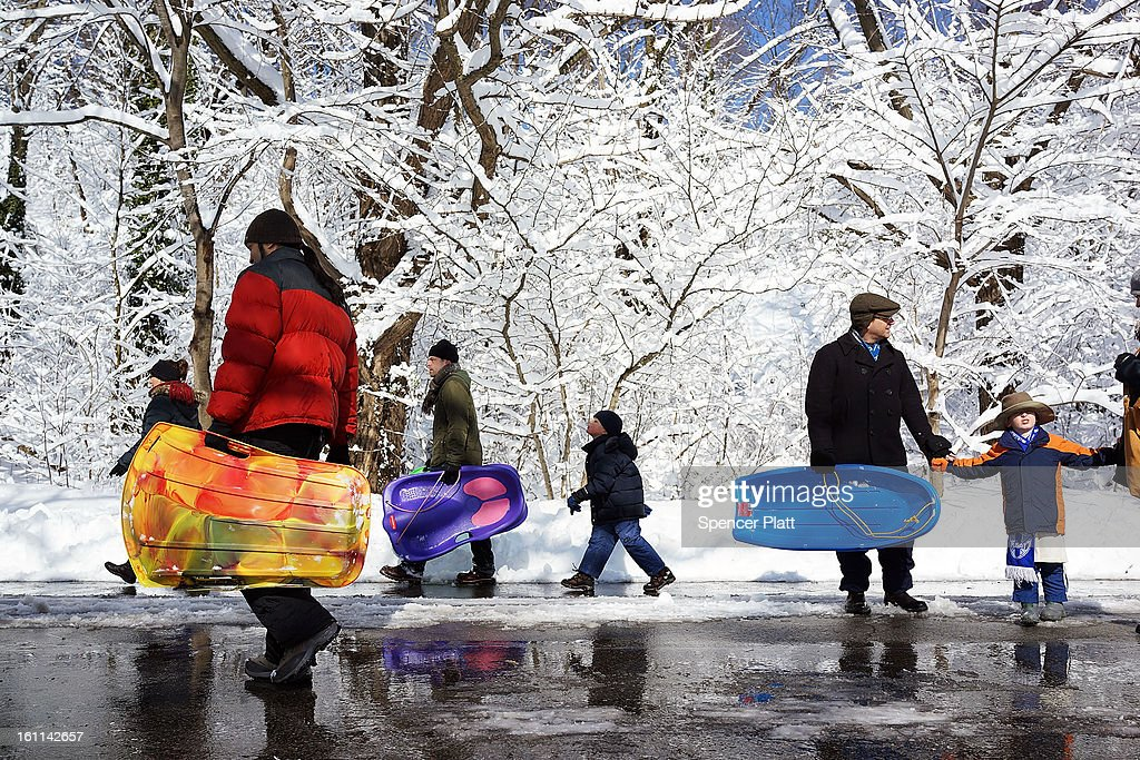 People walk with sleds through a snowy Prospect Park in Brooklyn the morning after a massive snow storm on February 9, 2013 in New York City. New Yorkers woke up to over 10 inches of snow Saturday morning while parts of New England received over thirty inches following a storm that brought high winds and blizzard like conditions to the region.