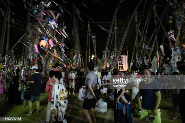 People walk with tanabata ornaments at the shrine compound during the annual Suhoutei Festival at Iminomiya Shrine on August 7, 2019 in Chofu,...