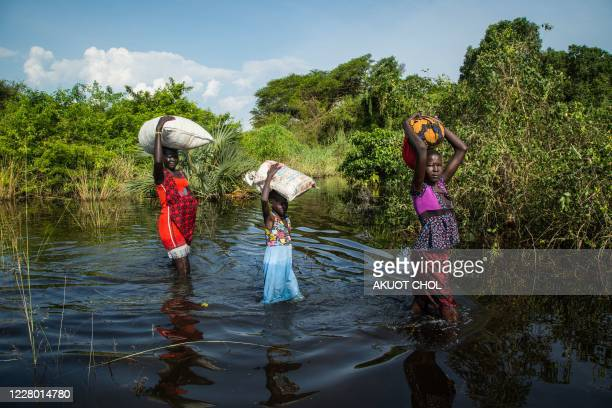 People walk with their belongings in a flooded area after the Nile river overflowed after continuous heavy rain which caused thousands of people to...