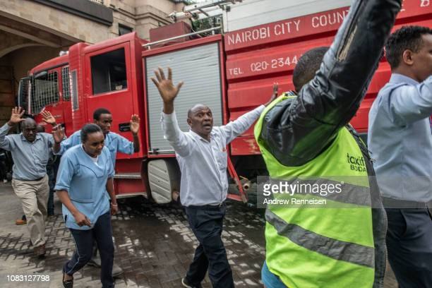 People walk with their hands up after being rescued from the Dusit Hotel on January 15 2018 in Nairobi Kenya A current security operation is underway...