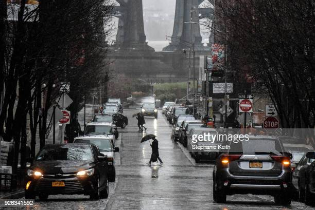 People walk with umbrellas during a large storm on March 2 2018 in the Brooklyn borough in New York City A nor'easter is set to slam the East Coast...