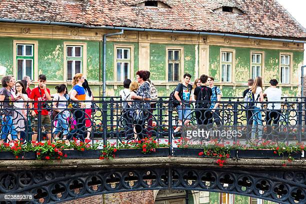people walking across liar's bridge in sibiu, transylvania, romania - sibiu stock photos and pictures