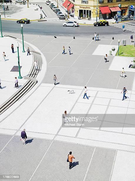 people walking across plaza