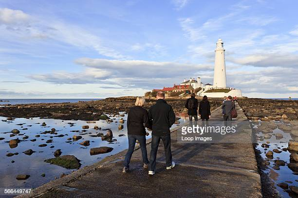 People walking across the concrete causeway to St Mary's Lighthouse near Whitley Bay