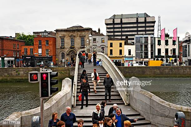 People walking across the Halfpenny Bridge over the Liffey River Dublin Republic of Ireland Europe