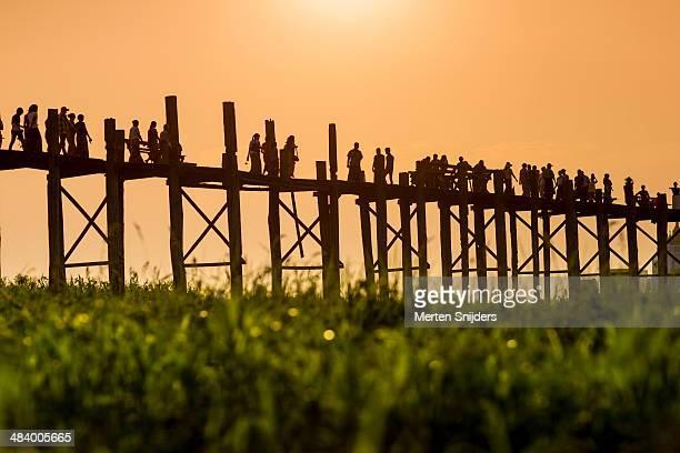 people walking across u bein bridge - merten snijders imagens e fotografias de stock