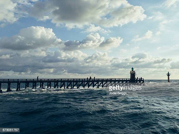 People walking along a jetty towards a lighthouse
