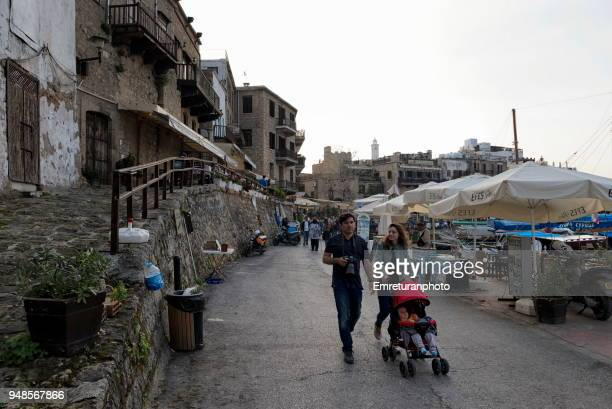 people walking along girne marina on a spring day. - emreturanphoto stock pictures, royalty-free photos & images