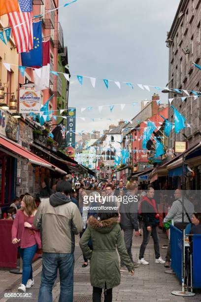 people walking along shop street in galway, ireland - county galway stock pictures, royalty-free photos & images