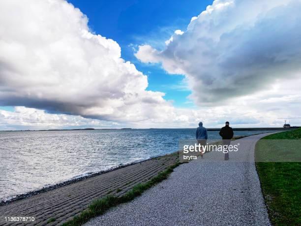 people walking along the eastern scheldt in  wemeldinge,zeeland, netherlands - levee stock pictures, royalty-free photos & images