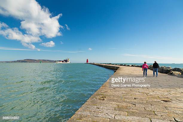 People walking along the Great South Wall towards Poolbeg Lighthouse in Dublin, Ireland